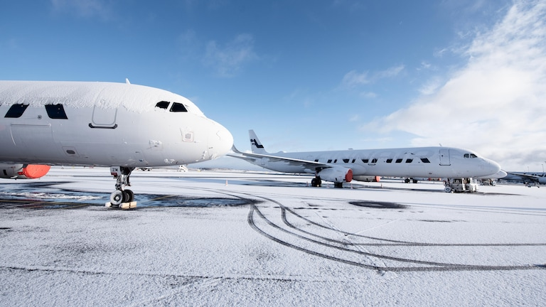 Two Finnair aircraft parked near an icy runway